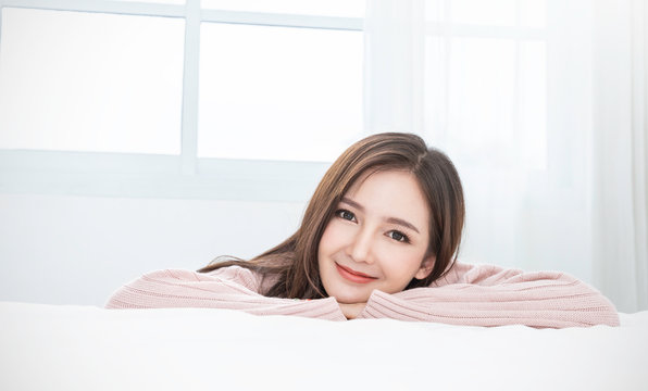 Portrait of young beautiful sexy asian woman relax in her bedroom. Smile happy face asian girl on white background. Beauty treatment perfect clear skin japanese korean makeup lifestyle winter concept
