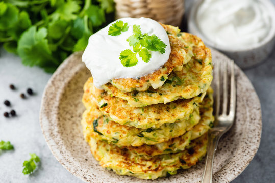 Zucchini fritters or pancakes stack with sour cream on top. Healthy vegetable patties