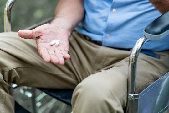 Senior man holding medication pill. In wheelchair. Caucasian male.