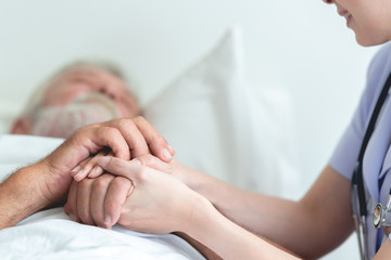 Senior man in bed with nurse in retirement home. Caucasian male with asian woman. Comforting hands with copy space.