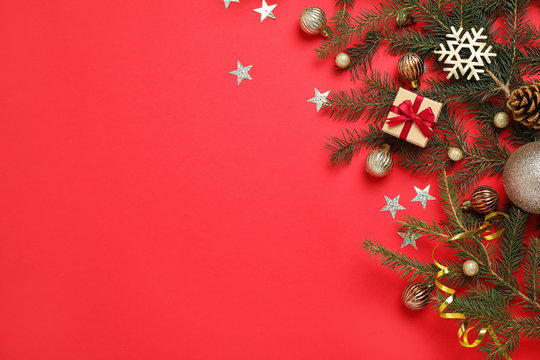 Fir branches with Christmas decoration on red background, flat lay. Space for text