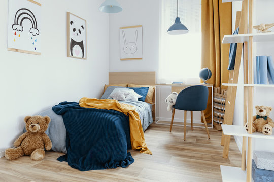 Workspace with desk and chair in elegant teenager's room with blue and orange design