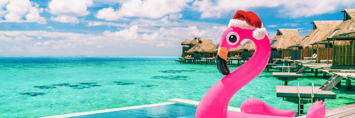 Christmas beach summer vacation winter holiday destination panoramic banner. Pink flamingo pool float with santa hat travel background for winter holidays.