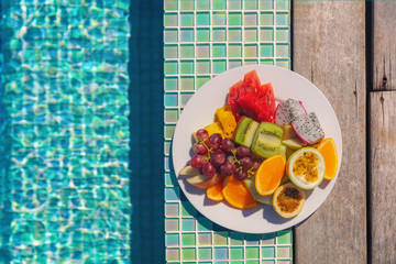 Vacation food fruit plate breakfast top view by the hotel swimming pool background. Luxury resort...