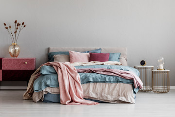 Pastel pink, beige and blue bedding on king size bed in trendy bedroom interior, copy space on empty grey wall