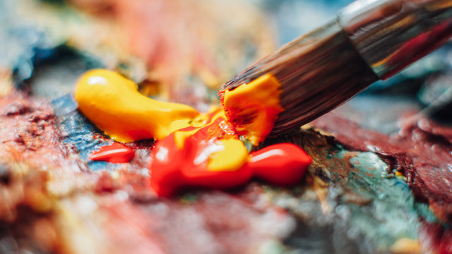 Creative artist using paintbrush to mix yellow and red oil paint on colorful palette.