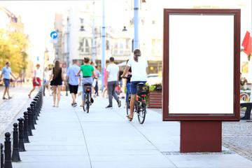 Bilbord reklamowy w centrum miasta Wrocław, w tle rowerzyści na rowerach.