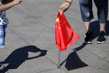 A mother holds Chinese flags as she helps her son take a picture on Tiananmen Square in Beijing