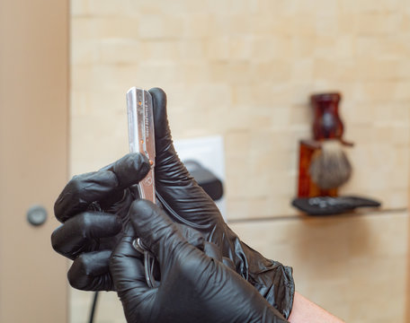 Hands with straight razor, close up view. Hands in black rubber gloves, photographed in hairdressing saloon. Hairstylist preparing for shaving. Selective soft focus. Blurred background