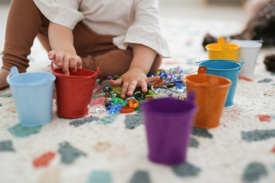Toddler girl plays with beads and multicolored