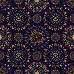 Seamless mandala pattern in shades of gold, navy, purple and turquoise.