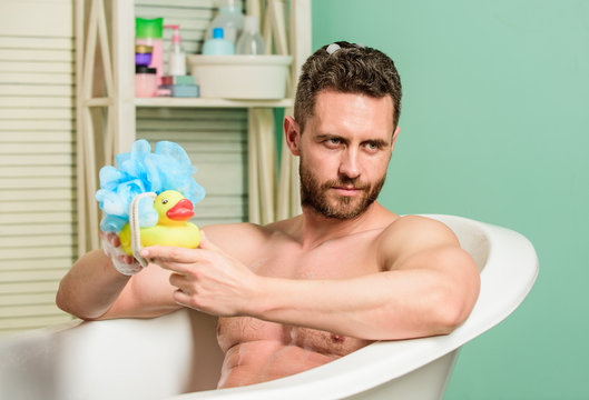 funny duckling. playful mood. macho enjoy bath. Sexy man in bathroom. Sex and relaxation concept. man wash muscular body with foam sponge. Wash off foam with water carefully. Macho naked in bathtub