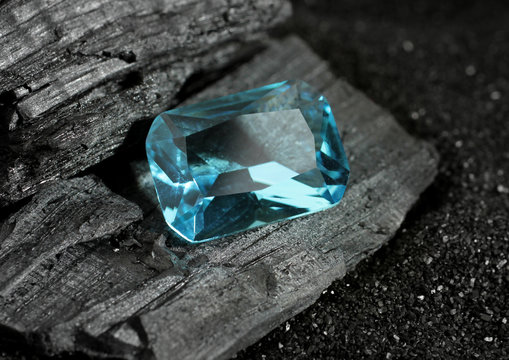 faceted blue jewelry gemstone aquamarine on black coal background