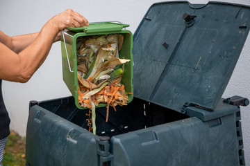female emptying a bucketful of kitchen waste to the compost bin
