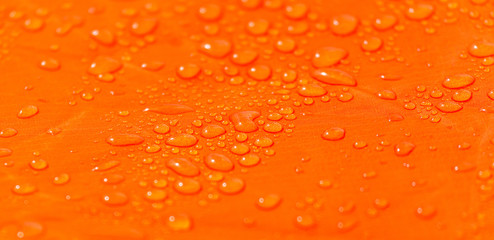 Raindrops on a tent of orange color as an abstract background