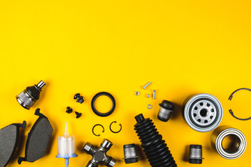 Set of car parts for maintenance on yellow background