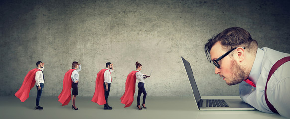 Stressed business man being helped online by professional team of super hero people