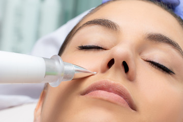 Cosmetic laser pen reducing wrinkles on female face.