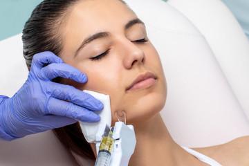 Therapist lightening pigmented skin on female cheek.