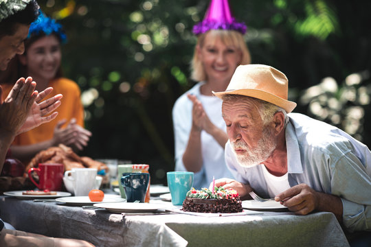 Senior birthday in. backyard tropical garden. White, asian senior man and woman with young couple. Enjoying a birthday party at home garden. Blowing his cake.