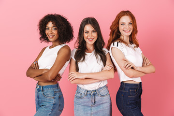 Positive young three multiethnic girls friends posing isolated over pink wall background.