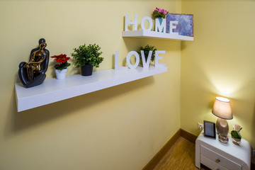 "White wooden signs ""HOME"" and ""LOVE"" on the shelves in the room. Lamp on the bedside."