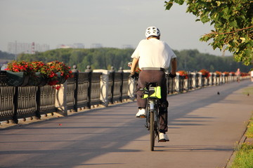 A man in protective helmet ride on bicycle on an asphalt road in Park on a summer day - sporty lifestile