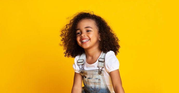Laughing cute afro girl portrait, yellow background