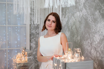 A beautiful happy woman in a white evening dress is standing near the Christmas garland and decorations. New Year celebration Fototapete