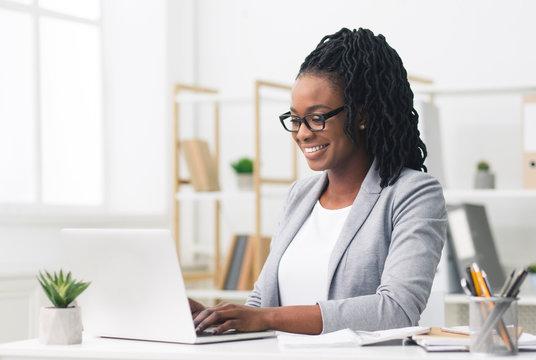 Black Female Entrepreneur Using Laptop In Modern Office