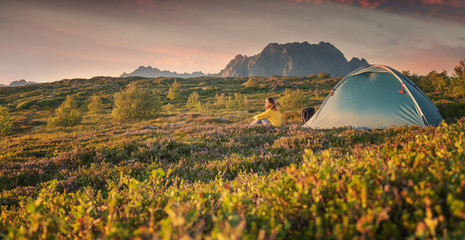 Wall Mural - A young woman is relaxing next to a tent on the Lfoten Islands in Norway with views of the sunset and mountains, enjoying the view