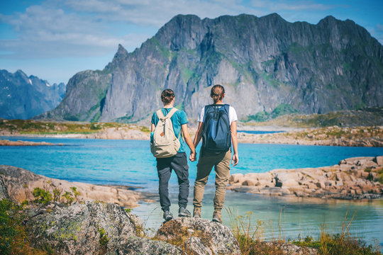 Two girls stand holding hands on the background of the Lofoten Islands, traveling to Norway, Scandinavia northern Europe