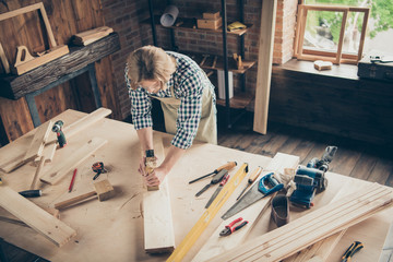 Above high angle view of his he nice attractive handsome blond guy skilled artisan builder making new house using instrument at industrial brick loft style interior workplace