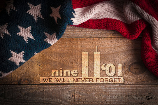 A scarf with the colors of the American flag on a wooden table and an inscription in memory of September 11th. Patriot day 2019.
