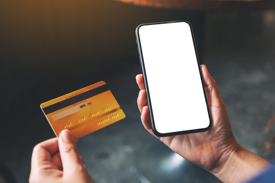 Mockup image of a hands holding credit card and a black mobile phone with blank desktop screen