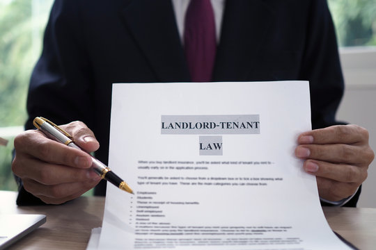 House salesman is showing Landlord-Tenant Law document.