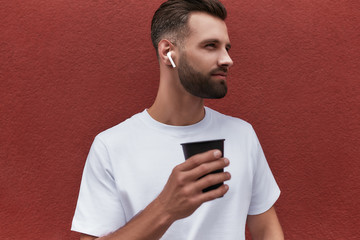 Wall Mural - Thinking about life. Handsome bearded man in headphones holding cup of coffee and looking aside while standing against red wall outdoors