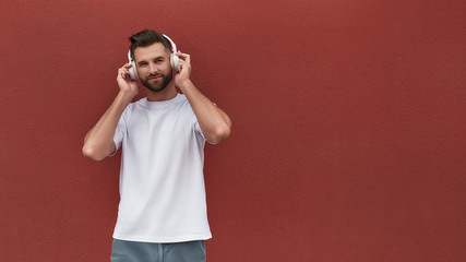 Wall Mural - Favourite playlist. Portrait of handsome man in headphones listening to the music and looking at camera while standing against red wall outdoors