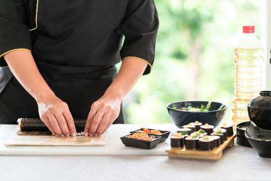 Chef preparing sushi. Asian woman chef in black uniform, completing the roll and put small rice on.