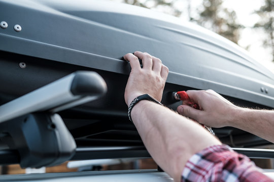 Men's hands cover the assembled, roomy trunk or cargo box on the roof of the car, for safety, before leaving for a family vacation.