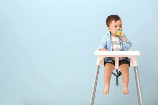 Cute little boy with nibbler sitting in high chair against color background