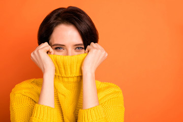 Fototapeta Close up photo of cute nice charming girl hiding from cold by wrapping up in collar while isolated with orange background obraz