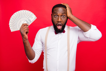 Photo of dark skin guy showing fan of usa bucks don't know how to spend it formal wear isolated red background Fototapete