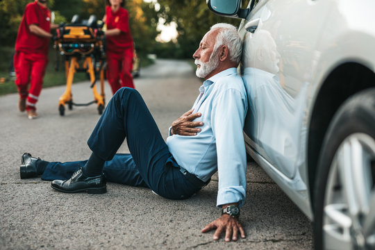 Elegant senior man with heart attack symptoms sitting on the road emergency medical service workers trying to help him. Driver assistance service.