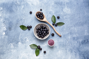 Fotobehang - Acai berries with powder on color background