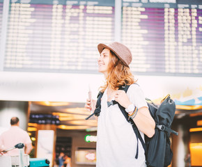 Happy young girl traveler at the airport with a backpack on the background of a departures board