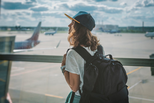 young girl traveler with backpack at the airport on the background of the takeoff field