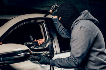 The robber in Balaclava threatening with a knife takes away a bag from the driver of a car. The concept of crime.