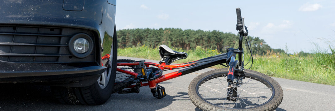 Children's bicycle accident with car on the street. Panoramic image