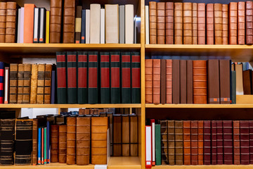 Antique leather cover books on wooden bookshelf in university public library. Reading philosophy or...